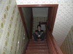 Paranormal Rona sitting at the top of the staircase