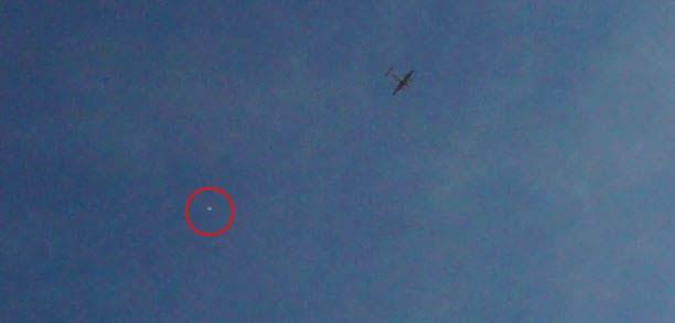 Airplane with strange object near it
